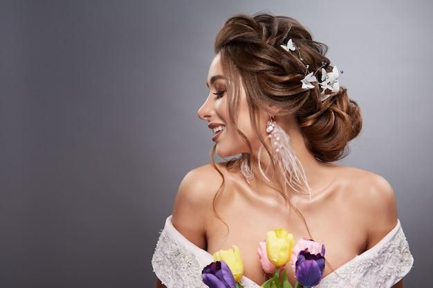 Profil roześmianej panny młodej z otwartymi ramionami i kwiatami na szarym tle