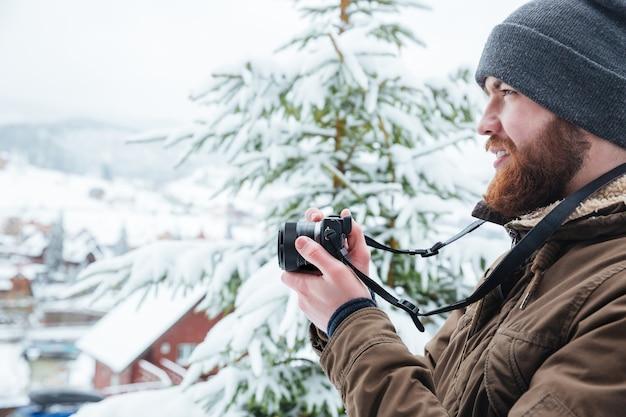 Profil skupionego młodego mężczyzny robiącego zdjęcia
