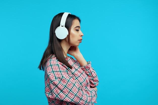 Profil słodkiej dziewczyny nosi białe słuchawki słucha muzyki z zamkniętymi oczami