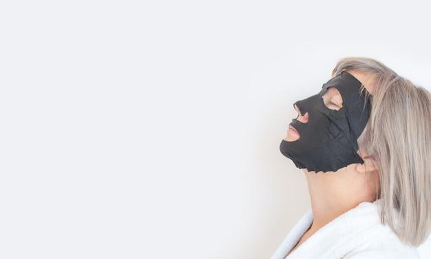 Profil starszej kobiety, nakłada na twarz czarną maskę kosmetyczną. koncepcja anty wieku. dojrzała kobieta twarz po zabiegu uzdrowiskowym. zabiegi kosmetyczne spa. miejsce na tekst