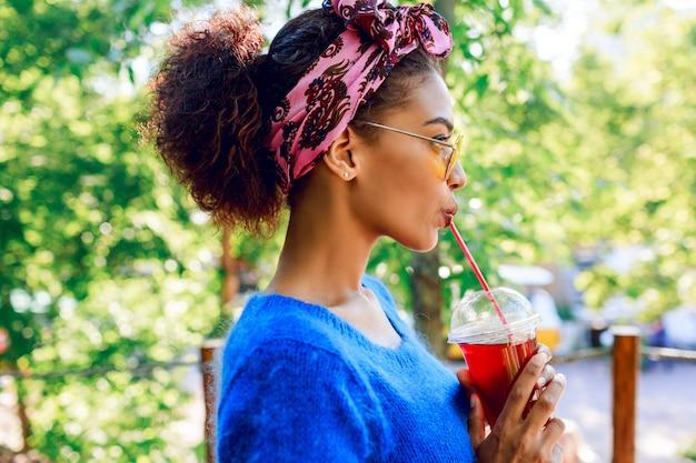 Profil szczęśliwa czarna kobieta ze stylową opaską patrząc na horyzont i trzymając na rękach wiśniową lemoniadę.