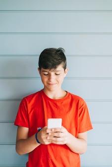 Profil szczęśliwy mężczyzna nastolatek sms-y na smartfonie