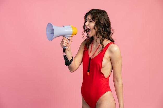 Profil uroczej dziewczyny w czerwonym kostiumie kąpielowym głośno przemawia do głośnika na różowym tle. ratownik zgłasza niebezpieczeństwo