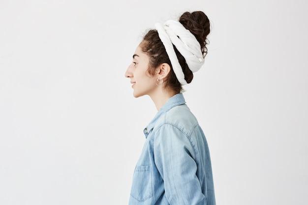 Profil uroczej stylowej dziewczyny z hairbun, ubranej w szmatę i dżinsową koszulę, uśmiecha się przyjemnie, pozuje na białej ścianie z miejscem na reklamę. pojęcie piękna i młodości