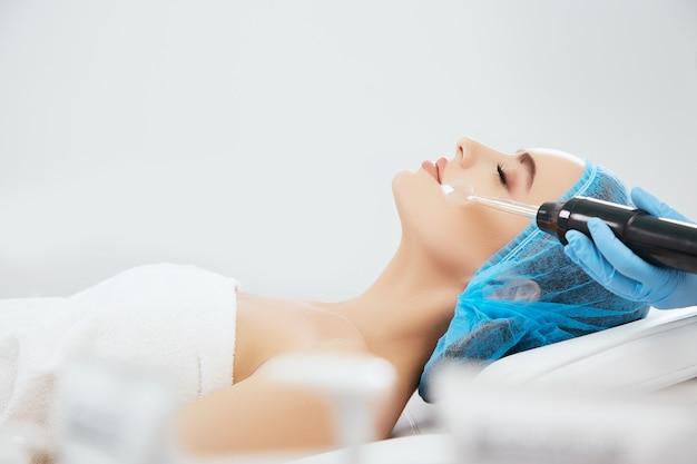 Profil uśmiechnięta kobieta w niebieskiej czapce leżącej na kanapie w klinice kosmetologicznej z zamkniętymi oczami. ręce lekarza w niebieskich rękawiczkach wykonujących procedurę darsonwalizacji