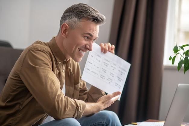 Profil uśmiechniętego mężczyzny przed laptopem