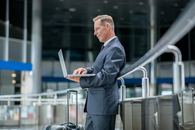 Profil uśmiechniętego mężczyzny z laptopem na lotnisku