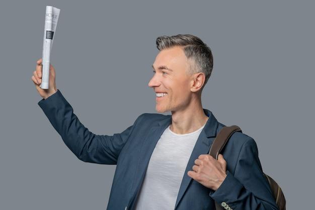 Profil uśmiechniętego mężczyzny z podniesioną gazetą w ręku