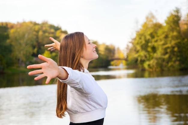 Profil. wesoła młoda dorosła dziewczyna pozuje w pobliżu jeziora. jesień, żółty, jesień. strzał na zewnątrz