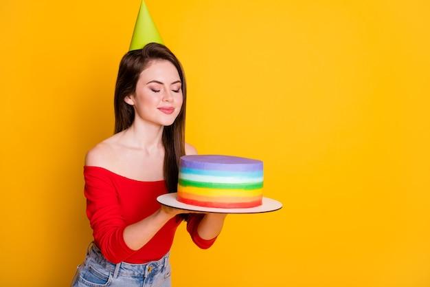 Profil widok z boku portret jej ona ładna atrakcyjna całkiem urocza marzycielska wesoła dziewczyna trzyma w rękach pachnący świeży pyszny tort na białym tle jasny żywy połysk żywy żółty kolor tła