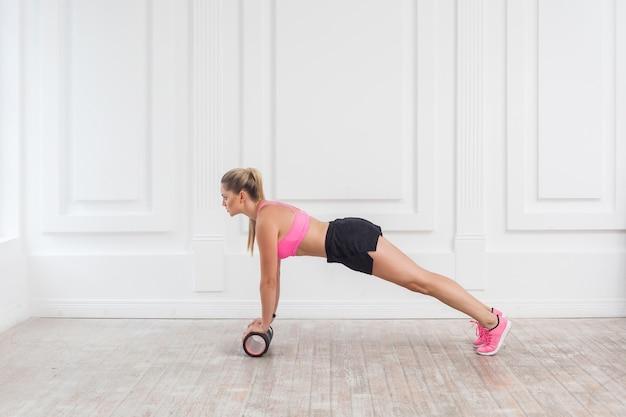 Profil widok z boku portret lekkoatletycznego blondynka młoda kobieta w fit nosić za pomocą wałka z pianki w siłowni do treningu do utraty wagi i robi deski. rehabilitacyjna medycyna sportowa. kryty, studio strzał,