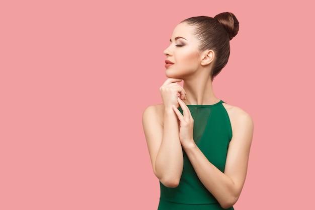 Profil widok z boku portret spokojnej poważnej pięknej młodej kobiety z kok fryzurę i makijaż w zielonej sukni stojącej z zamkniętymi oczami i dotykając jej podbródka. strzał studio, na białym tle na różowym tle.