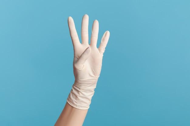 Profil widok z boku zbliżenie ludzkiej ręki w białych rękawiczkach chirurgicznych pokazując numer cztery 4 ręką.