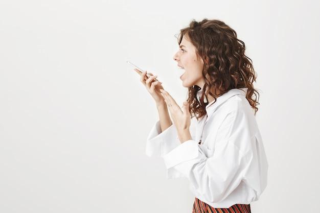 Profil wściekłej ładnej kobiety krzyczącej na przenośny głośnik, nagrywanie wiadomości