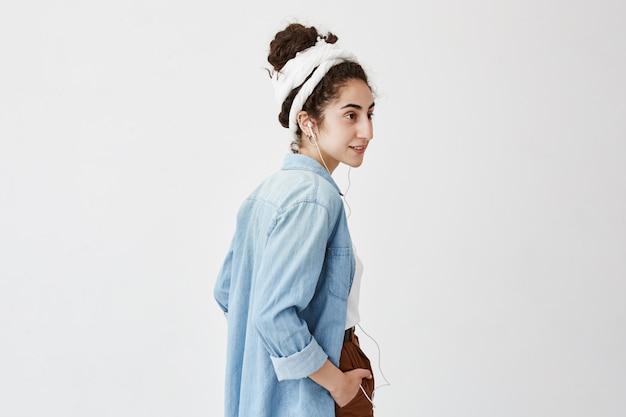 Profil żeńskiego nastolatka słucha muzyczna lub audio książka podczas gdy iść na uniwersytet, ma szczęśliwego wyrażenie, śmia się, odizolowywa przeciw biel ścianie. koncepcja muzyki i relaksu