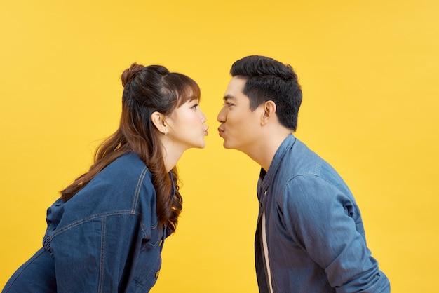 Profile dziewczyny i chłopaka, którzy całują się w powietrzu na żółto