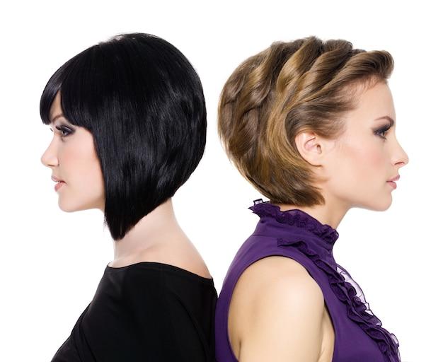 Profilowe twarze dwóch atrakcyjnych dorosłych dziewcząt stojących plecami do siebie