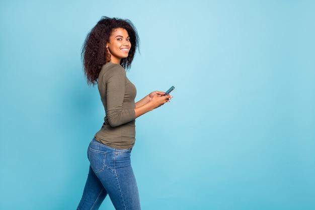 Profilowe zdjęcie pozytywnej wesołej mulatki używa swojego smartfona baw się w weekendy ciesz się czytaniem wiadomości na blogu aktualności w sieci społecznościowej noszą zielony sweter dżinsy na białym tle niebieski kolor ściana