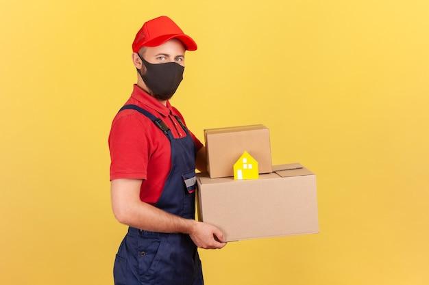 Profilowy mężczyzna dostarczający portret na twarzy trzymający kartony i papierowy dom