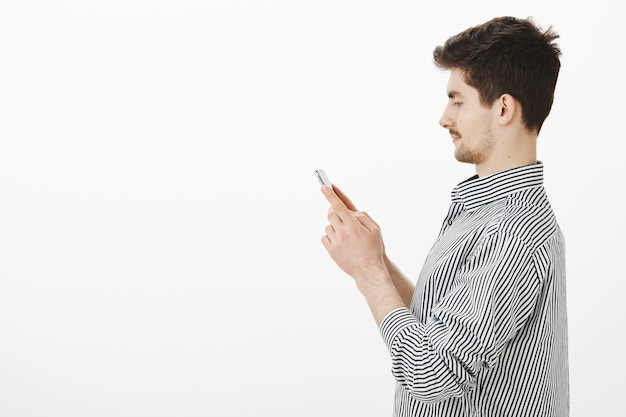 Profilowy portret beztroskiego szczęśliwego chłopaka rasy kaukaskiej z wąsami i brodą, trzymającego smartfona, patrzącego na ekran skupiony na ekranie, piszącego wiadomość do przyjaciela