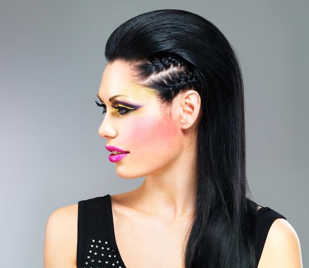 Profilowy portret kobiety z makijażem mody na twarzy i czarne proste włosy