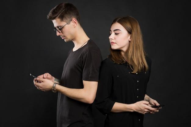 Profilowy portret młodego małżeństwa, przeglądającego informacje w pdas, stojącego tyłem, noszącego zwyczajne stroje na czarnej ścianie kolejne życie w sieciach społecznościowych