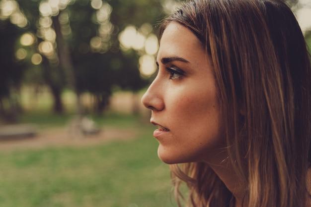 Profilowy portret młodej kobiety patrzącej prosto w naturę, stonowane odcienie i dodane ziarnistość filmu.