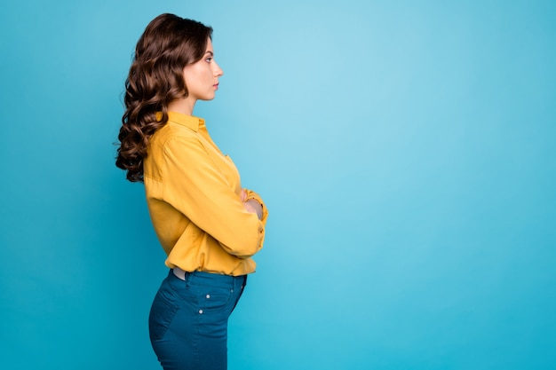 Profilowy portret niesamowitej kręconej kobiety biznesu trzymającej ręce skrzyżowane poważnie wyglądający koledzy nie lubią przychodzenia do pracy do późna nosić żółte spodnie koszuli.