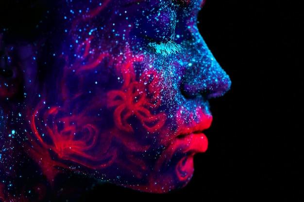 Profilowy portret pięknej obcej dziewczyny. ultrafioletowe body art niebieskie nocne niebo z gwiazdami i różowymi meduzami