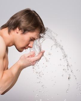 Profilowy portret przystojny mężczyzna do mycia twarzy wodą na szarej ścianie.