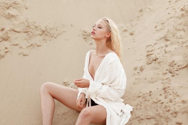 Profilowy portret seksownej gorącej blondynki w białej dużej koszuli, paląc siedząc na piasku. portret na zewnątrz.
