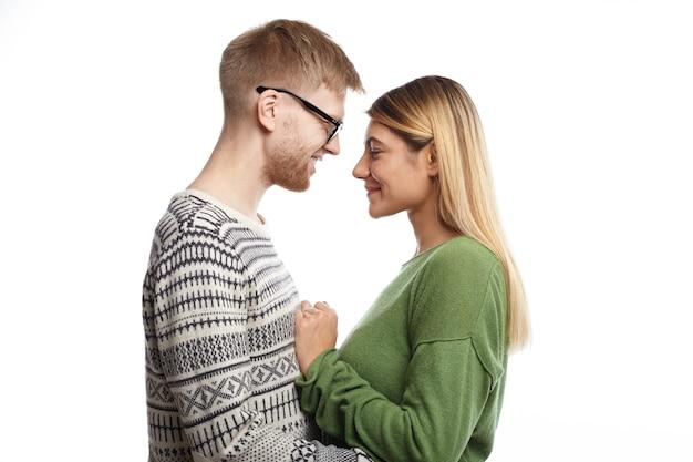 Profilowy portret szczęśliwego radosnego młodego mężczyzny i zakochanej kobiety stojących blisko siebie, przytulających się i rozmawiających, uśmiechających się radośnie, czujących się zrelaksowanych i beztroskich, ubranych w stylowe ubrania