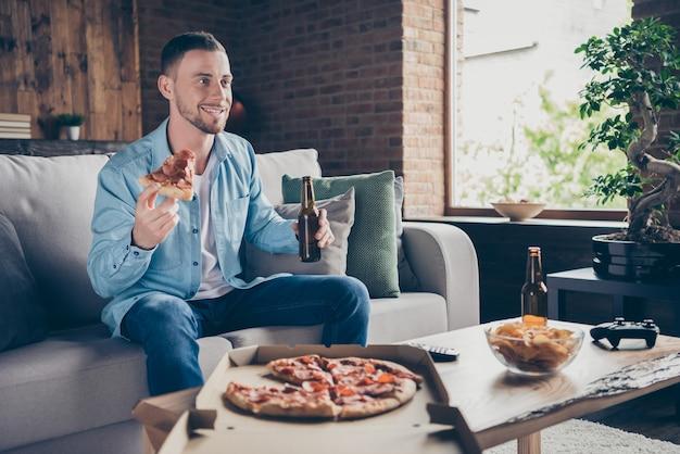 Profilowy przystojny facet ogląda telewizję je pizzę pije piwo