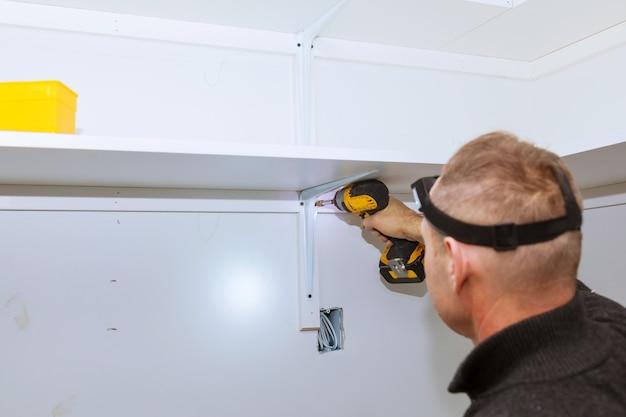 Profilowy widok dobra przyglądająca złota rączka robi niektóre świder ścianie instaluje półkę