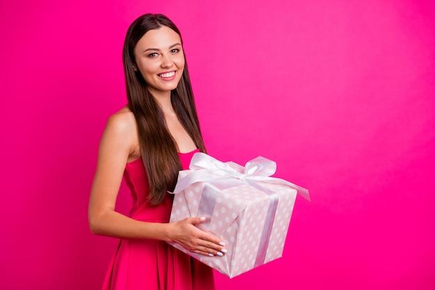 Profilowy widok z boku portret ładnej atrakcyjnej uroczej kochanej wesołej, długowłosej dziewczyny trzymającej w rękach świąteczny łuk wstążka pudełko na białym tle na jasnym, żywym połysku, wibrującym różowym kolorze fuksji