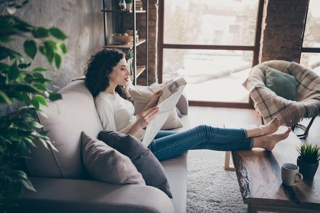 Profilowy widok z boku portret uroczej spokojnej dziewczyny siedzącej na kanapie czytającej wiadomości finansowe w nowoczesnym industrialnym loftowym stylu salonu w pomieszczeniu