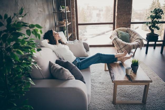 Profilowy widok z boku portret uroczej wesołej zadowolonej dziewczyny siedzącej na kanapie odpoczywającej spędzającej dzień w salonie w nowoczesnym stylu industrialnym loftowym