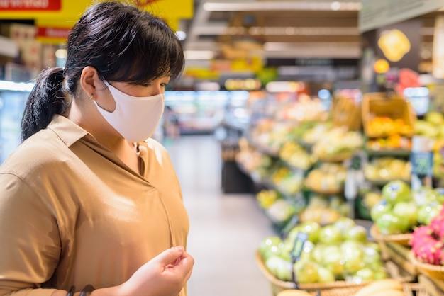 Profilowy widok z nadwagą azjatycka kobieta z maskowym zakupy wśrodku supermarketa