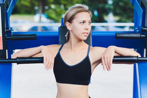Profilowy widok żeńska atleta robi niektóre tricep zamacza na parkowej ławce.