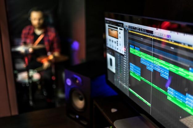 Program dźwiękowy na komputerze dla dj-a, autora tekstów, producenta do tworzenia nowych pomysłów w studiu stereo, podczas gdy młody człowiek gra na perkusji.