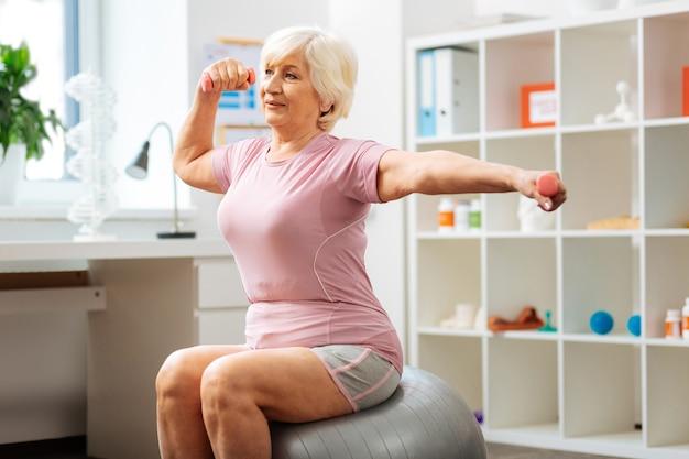 Program rehabilitacji. przyjemna aktywna kobieta trenująca sportowo podczas programu rehabilitacyjnego