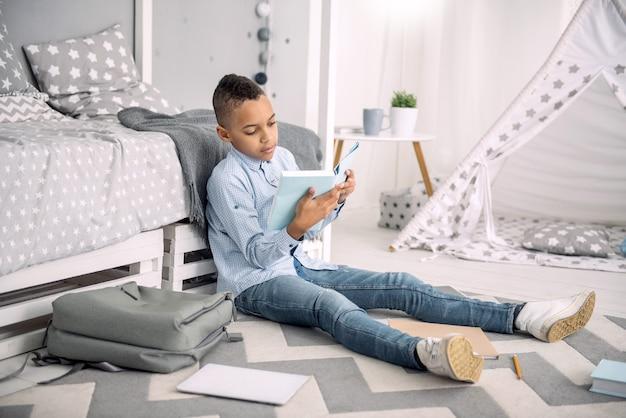 Program szkolny. atrakcyjny afro-amerykański chłopiec siedzi na podłodze podczas studiowania książki