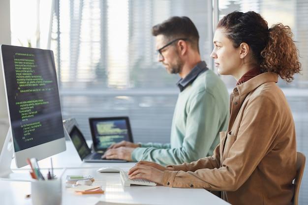 Programiści pracujący na komputerze w biurze it wpisujący kodowanie danych w oprogramowaniu