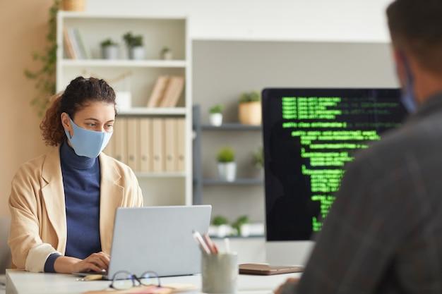 Programiści w maskach pracują przy stole na komputerach z kodami w biurze