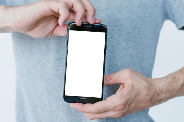 Programista aplikacji mobilnych. technologia i programowanie internetowe. rozwój oprogramowania dla smartfonów. mężczyzna trzyma inteligentny telefon z pustym białym ekranem.