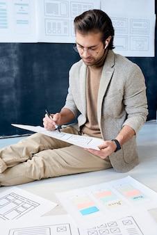 Programista aplikacji siedzący na podłodze