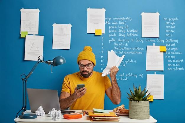 Programista it pracuje zdalnie z papierowymi dokumentami, sprawdza informacje przez telefon komórkowy w bazie danych, siedzi w przestrzeni coworkingowej