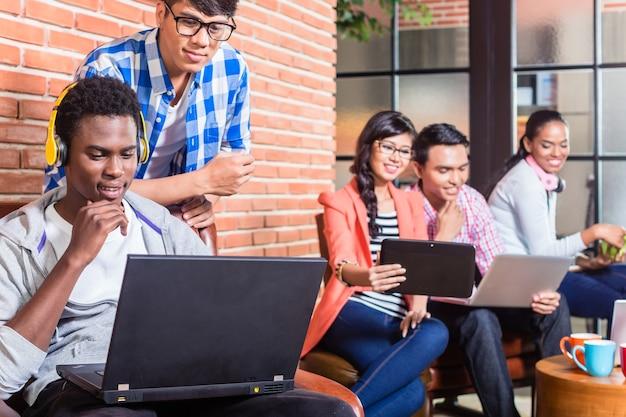 Programista komputerowy w start-upowej firmie kodujący obok współpracowników