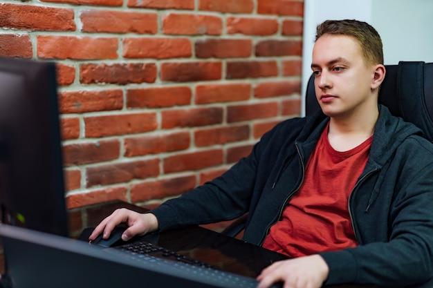 Programista pracuje komputer przy programowaniu na ścianie z czerwonej cegły. strona internetowa pracująca w oprogramowaniu tworzy pakiet firmowy.