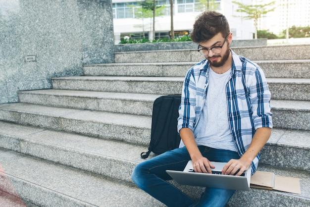Programista pracuje na komputerze na marmurowych schodach na ulicy